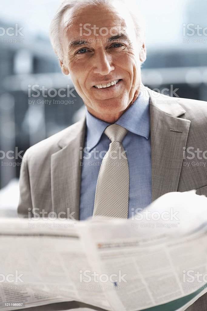 Happy elderly business man reading the daily newspaper royalty-free stock photo