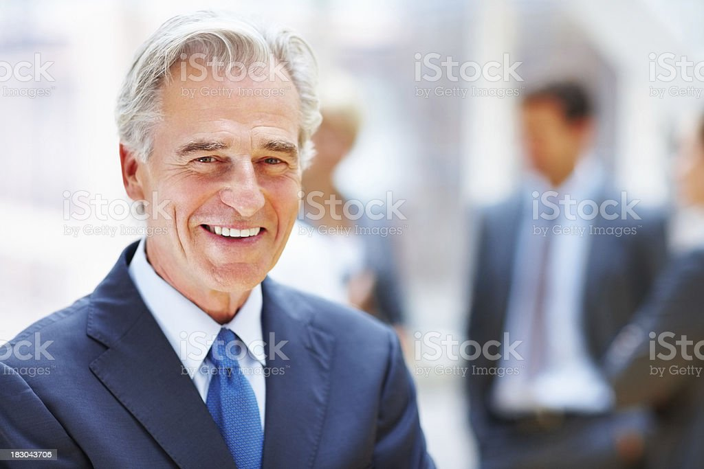 Happy elderly business man with his team in blur background royalty-free stock photo