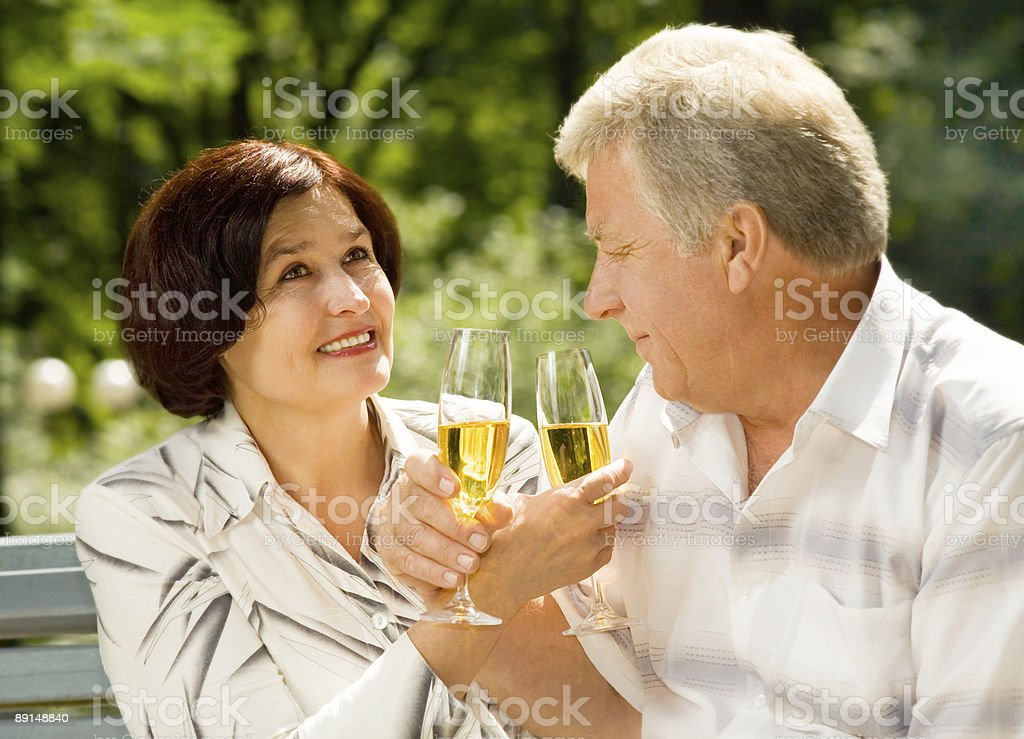 Happy elderly couple celebrating life event with champagne, outdoors royalty-free stock photo