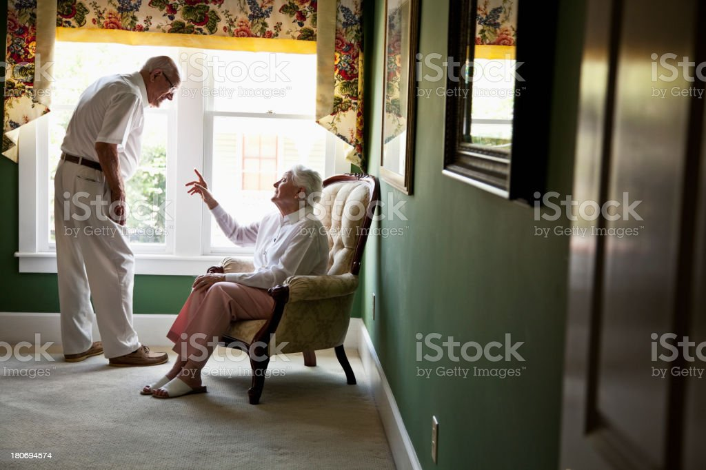 Happy elderly couple talking at home stock photo