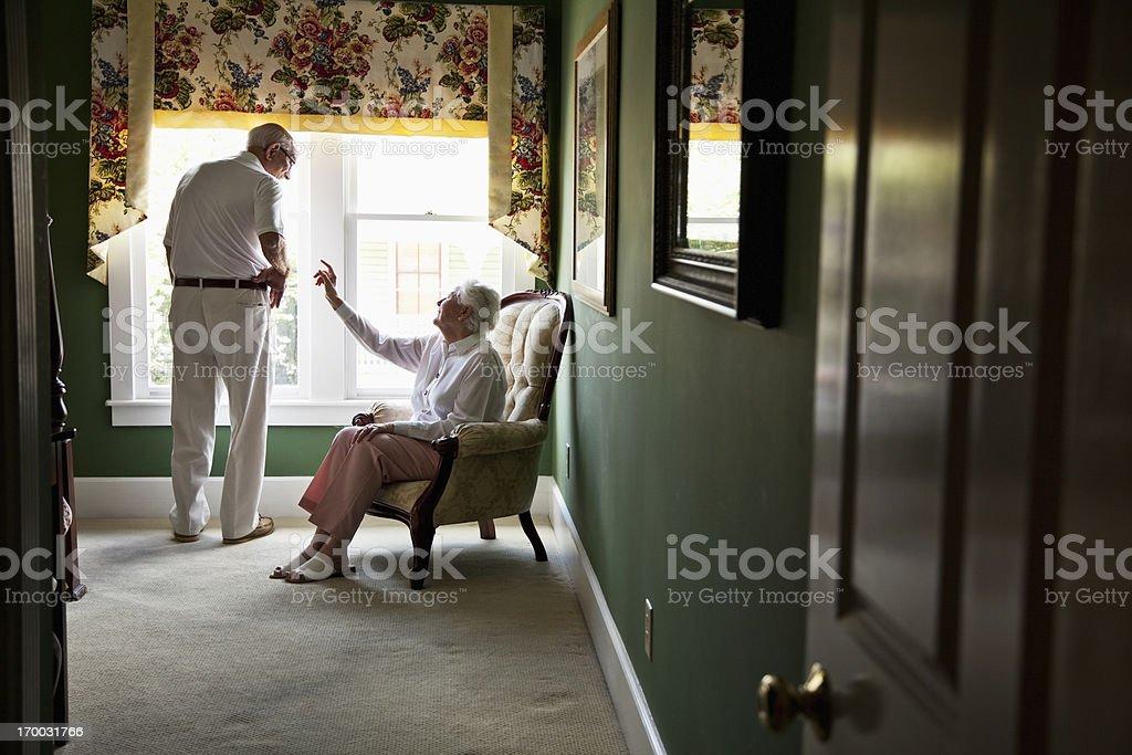 Happy elderly couple talking in bedroom stock photo
