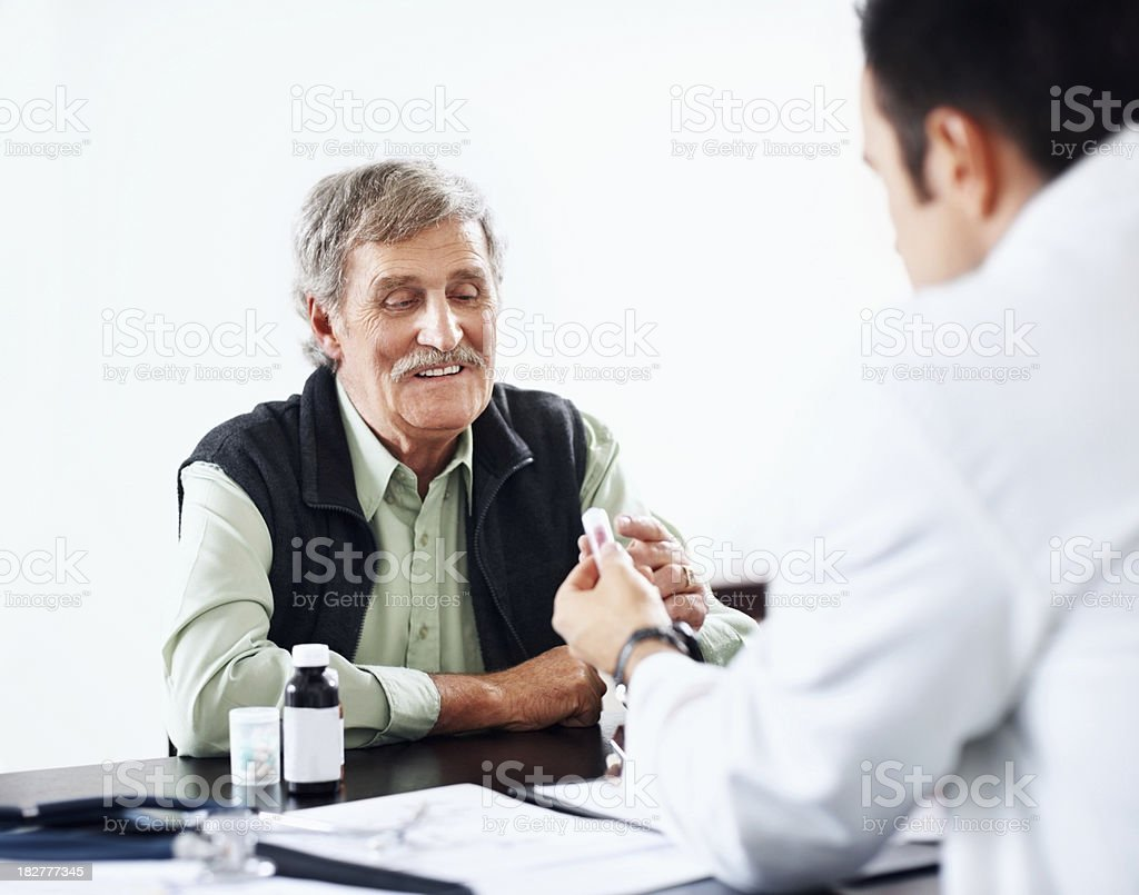 Happy elderly man being explained his medication by a doctor royalty-free stock photo