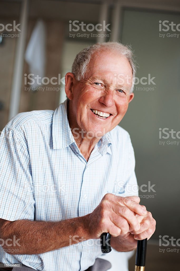 Happy elderly man with a walking stick royalty-free stock photo