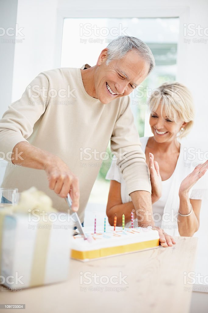 Happy elderly man with mature woman cutting the cake royalty-free stock photo