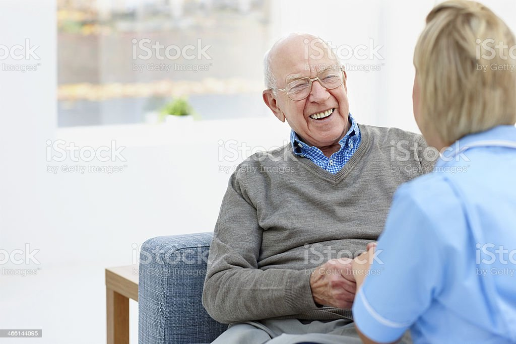 Happy elderly patient talking with nurse at home stock photo