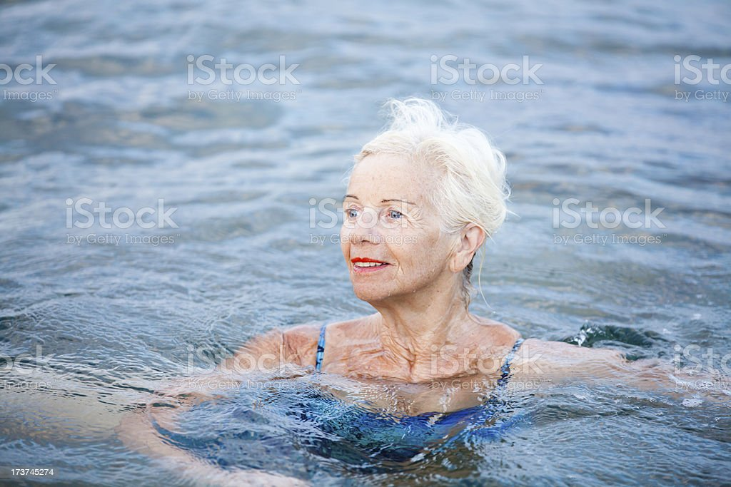 Happy elderly woman doing exercises in water royalty-free stock photo