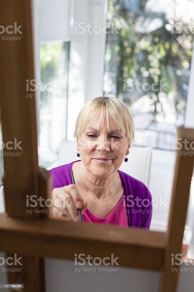Happy elderly woman painting for fun at home royalty-free stock photo