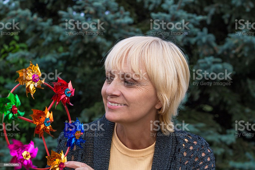 Happy elderly woman smiles and plays with propeller stock photo