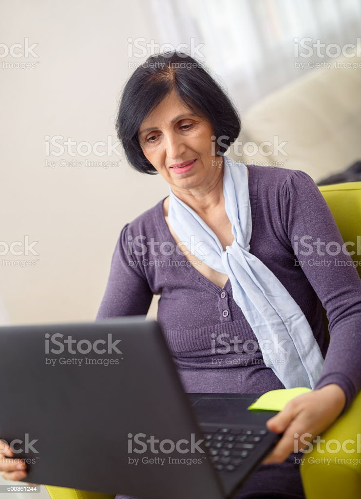 Happy elderly woman using laptop computer at home stock photo