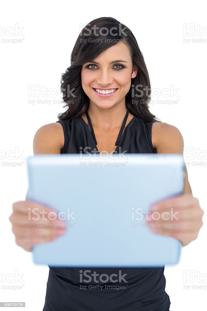 Happy elegant brown haired model holding tablet stock photo