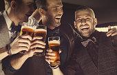 Happy elegant men toasting with beer