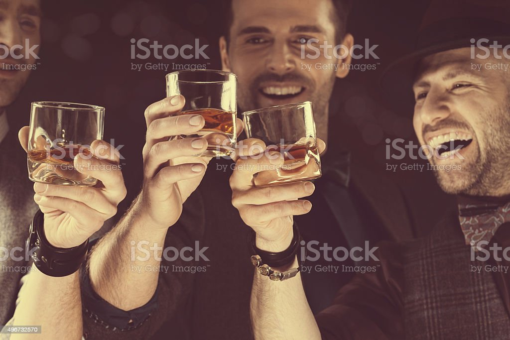 Happy elegant men toasting with whiskey stock photo