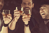 Happy elegant men toasting with whiskey
