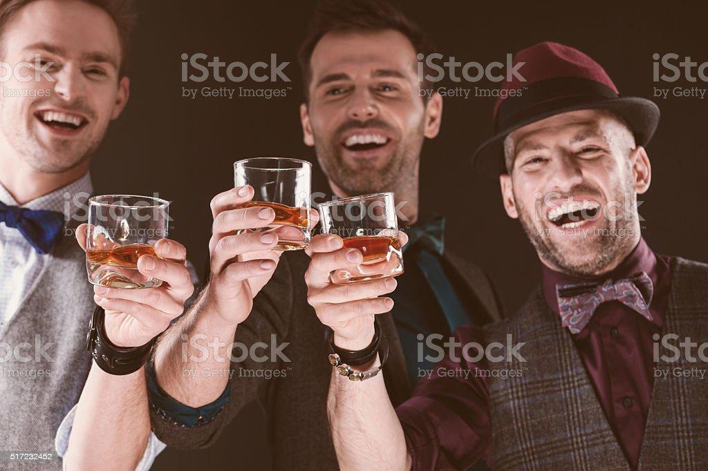 Happy elegant men toasting with whiskey stock photo
