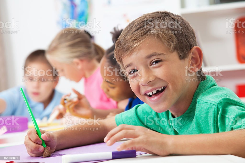 Happy elementary aged boy in art class at school royalty-free stock photo