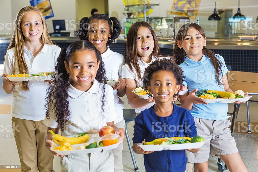 Happy elementary school girls in uniforms holding lunch trays stock photo