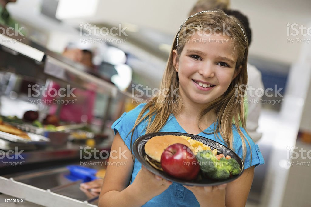 Happy elementary student with healthy lunch in school cafeteria royalty-free stock photo
