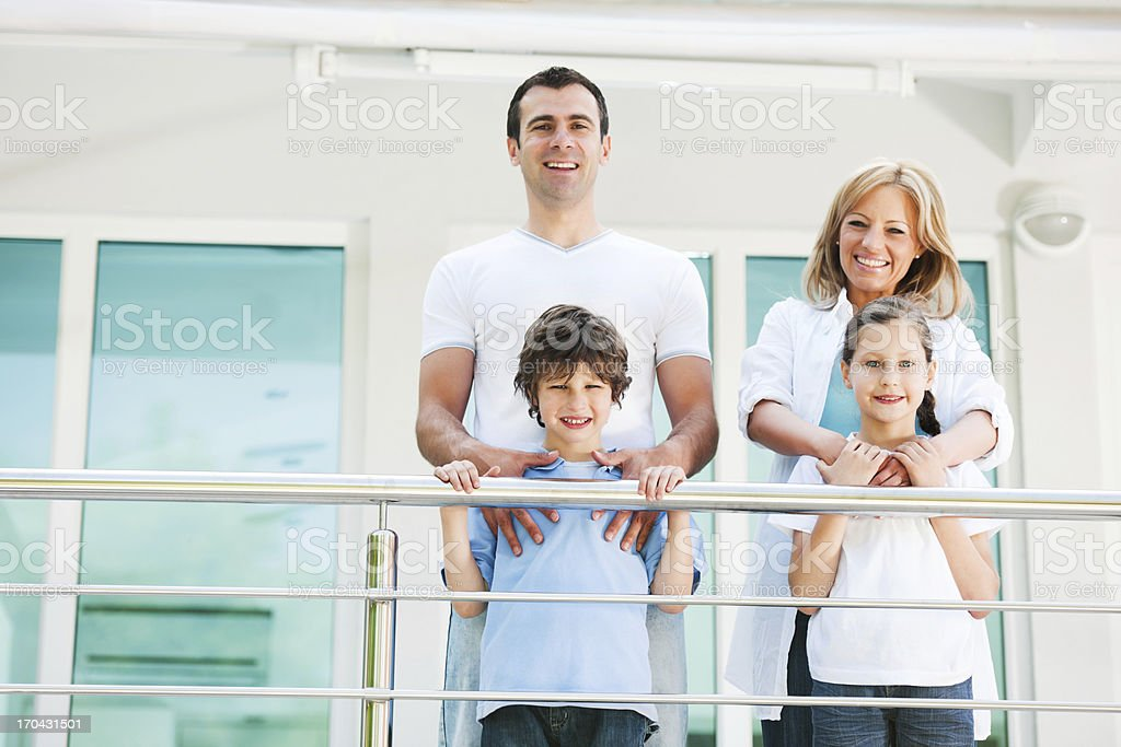 Happy embraced family standing on the balcony. royalty-free stock photo