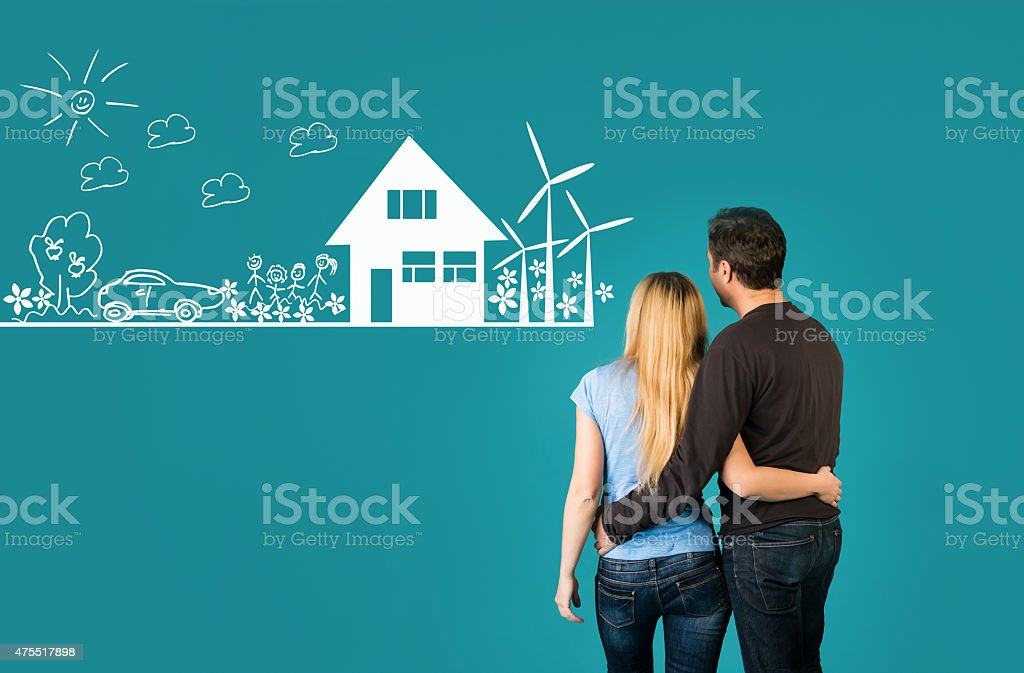 Happy embracing couple looking at eco friendly house sketch. stock photo