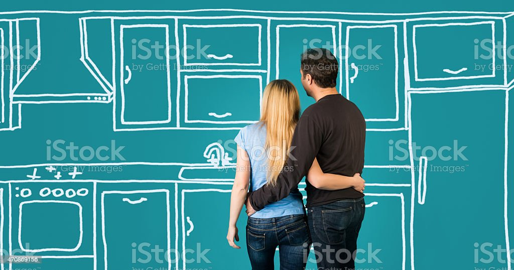 Happy embracing couple planning their home kitchen furnishing renovation. stock photo