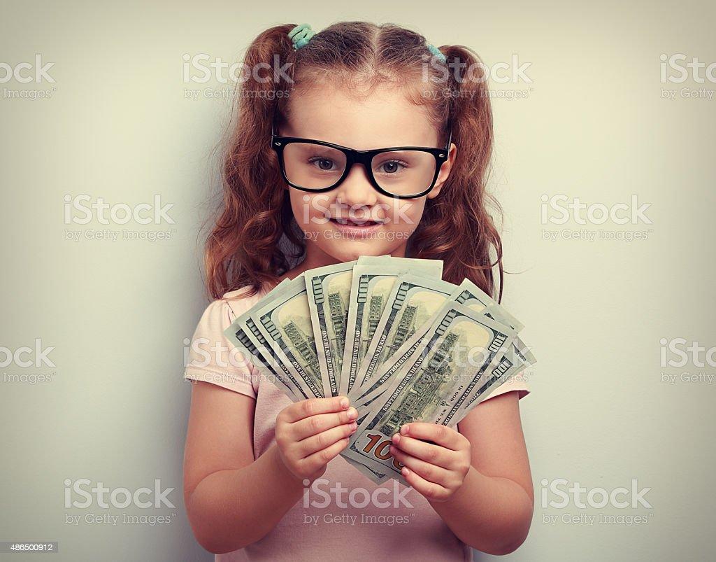 Happy emotion kid girl in glasses holding money stock photo