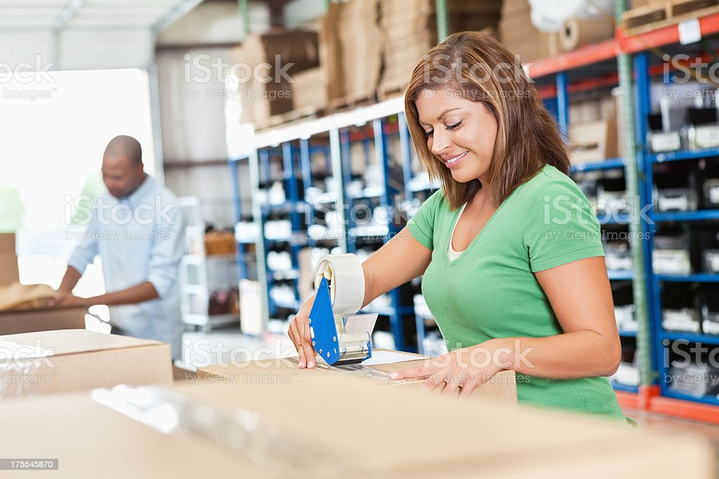 Happy employee assembling package in distribution warehouse royalty-free stock photo