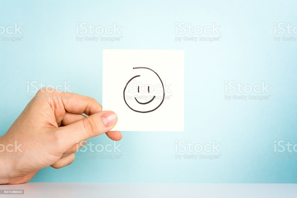 Happy employee. Happy emoticon or icon on blue background. stock photo