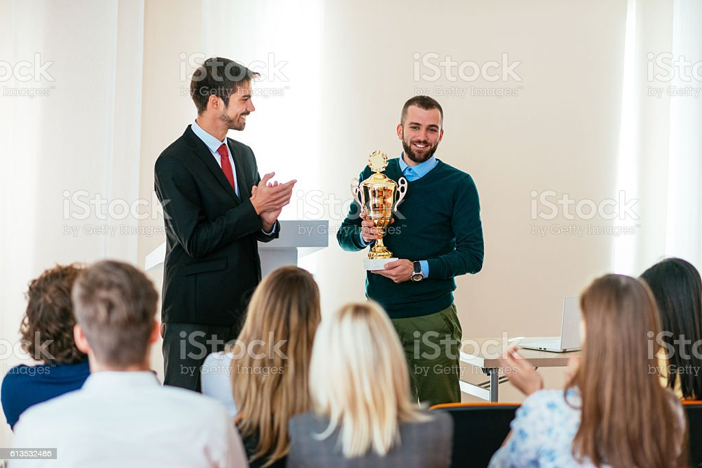 Happy employee of the month receives trophy from CEO stock photo
