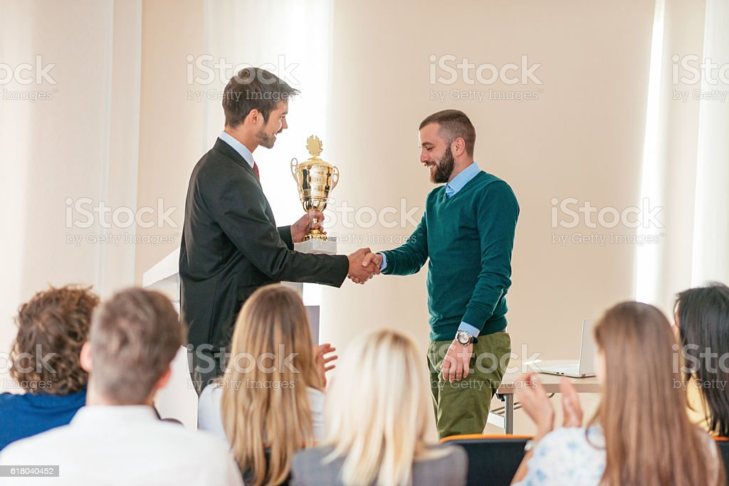 Happy employee of the month receives trophy from manager stock photo