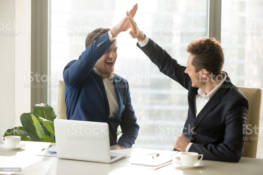 Happy employers celebrating achievements in work stock photo