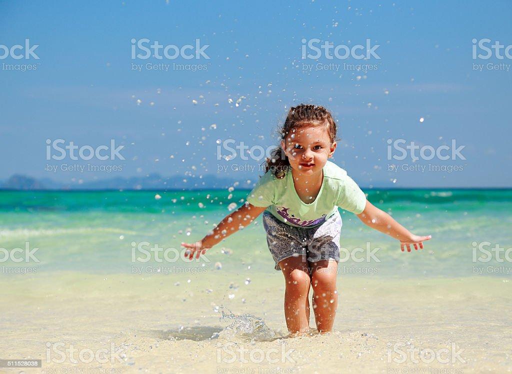Happy enjoying kid girl playing and splashing with water stock photo