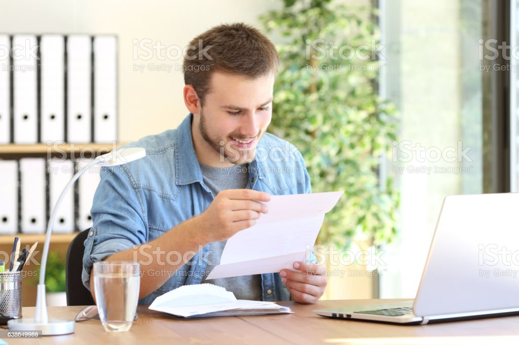 Happy entrepreneur reading a letter stock photo