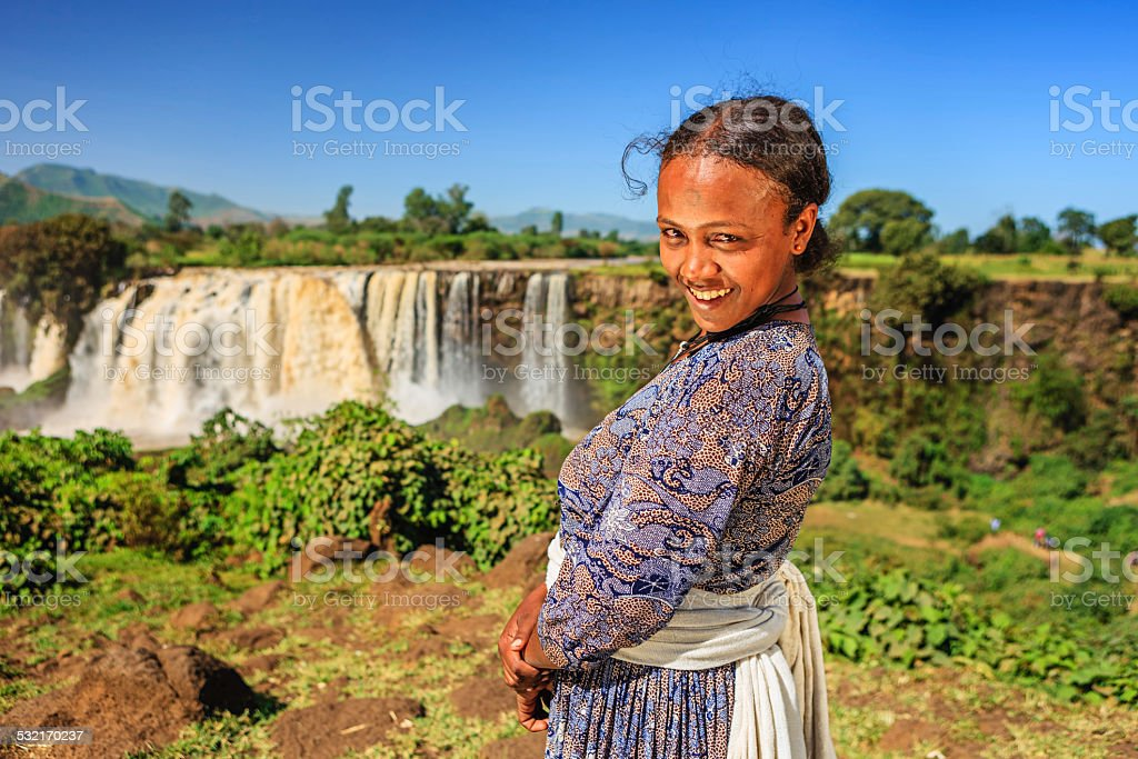 Happy Ethiopian woman at Blue Nile Falls stock photo