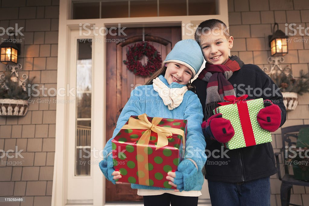 Happy, Excited Children Holding Christmas Presents in Front of House royalty-free stock photo