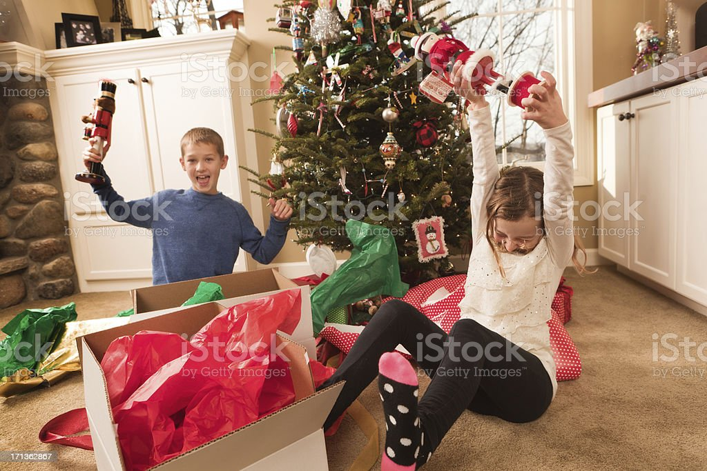 Happy Excited Children Opening Christmas Gifts in Front of Tree stock photo