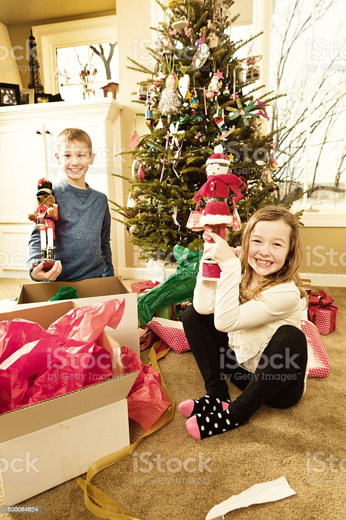 Happy Excited Children Opening Christmas Presents in Front of Tree stock photo