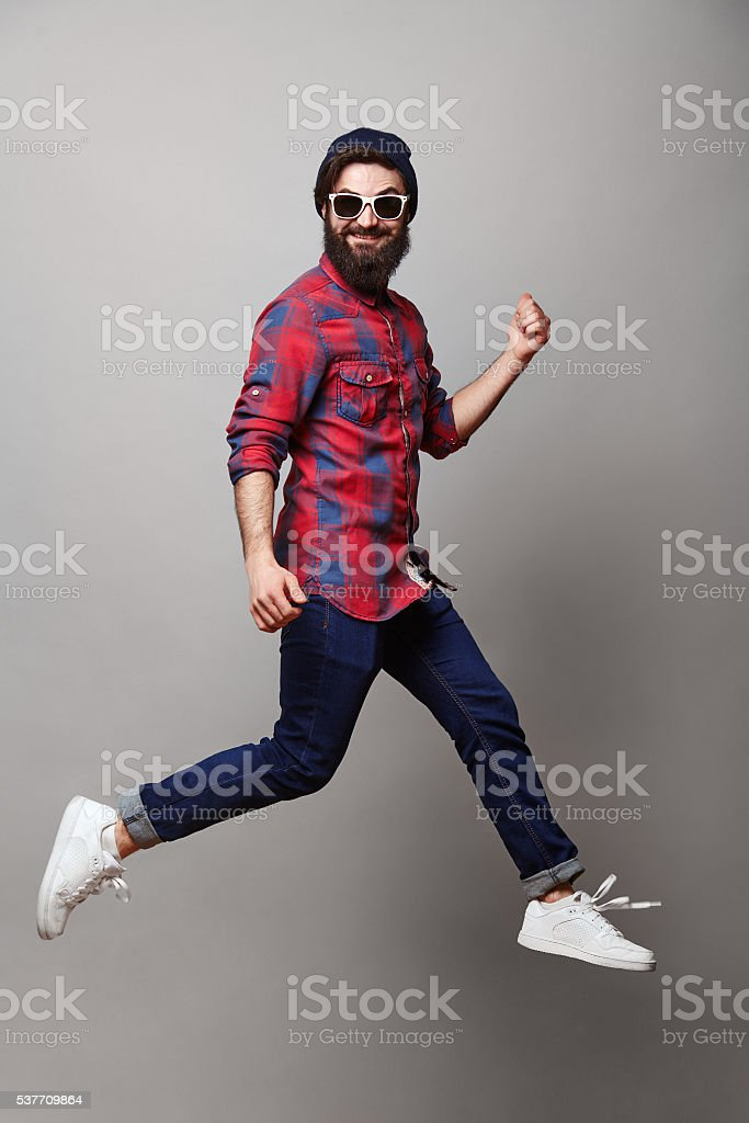 happy excited jmping young bearded man stock photo