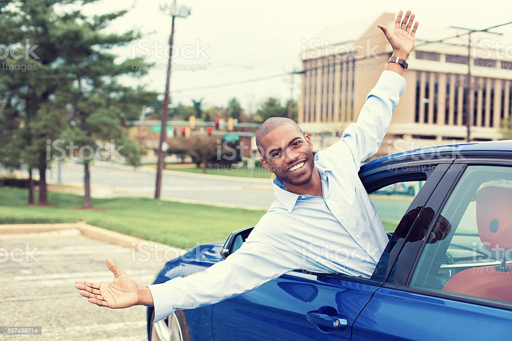 Happy excited man coming out of a car's window stock photo