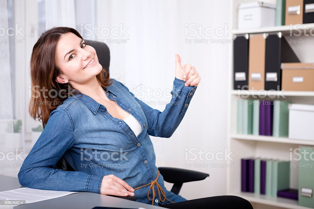 Happy excited woman giving a thumbs up gesture stock photo