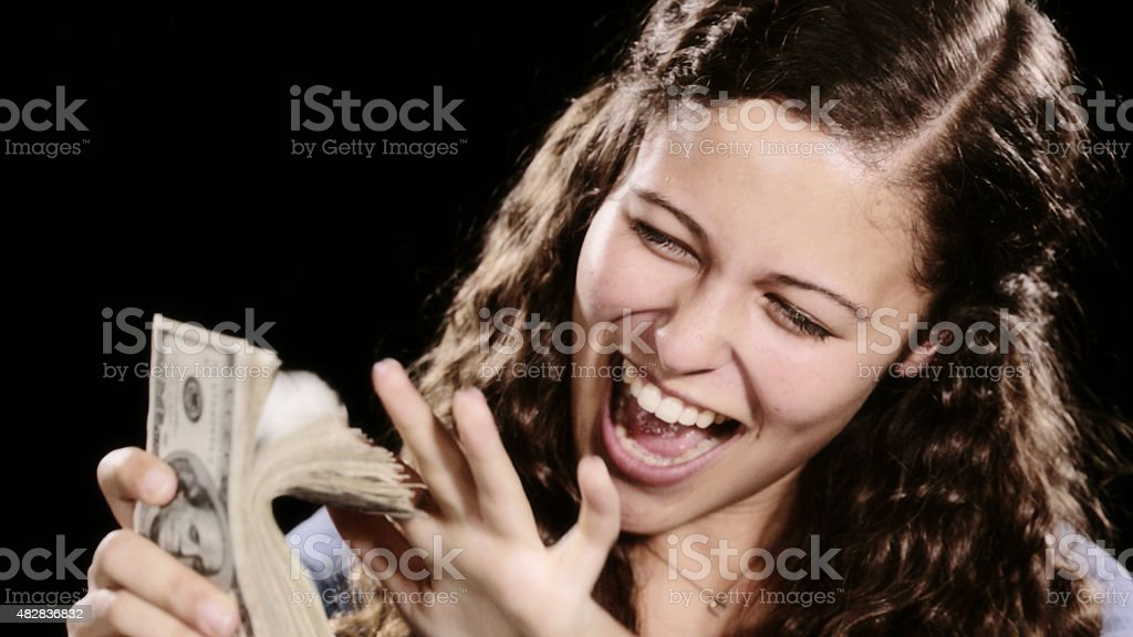 Happy, excited young woman flicking through sheaf of American dollars stock photo
