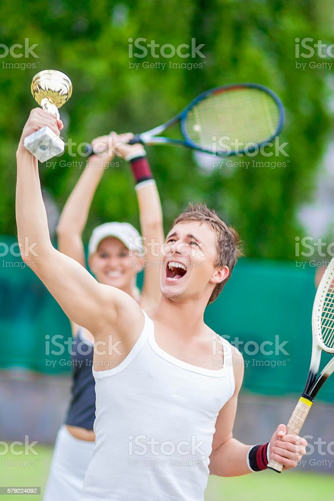 Happy Exclaiming Tennis Couple With Trophy stock photo