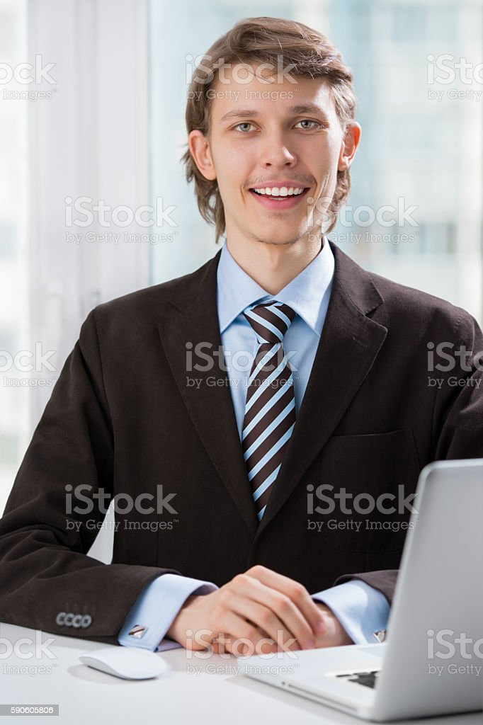 Happy executive sitting in front of laptop stock photo