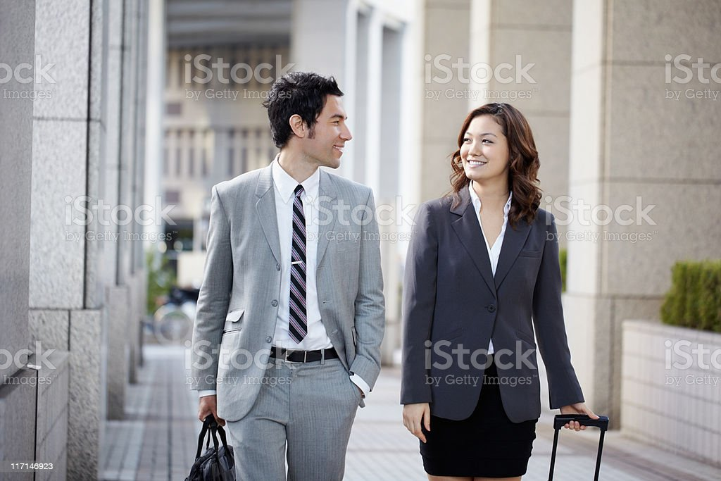 Happy executives looking at each other while walking on street royalty-free stock photo
