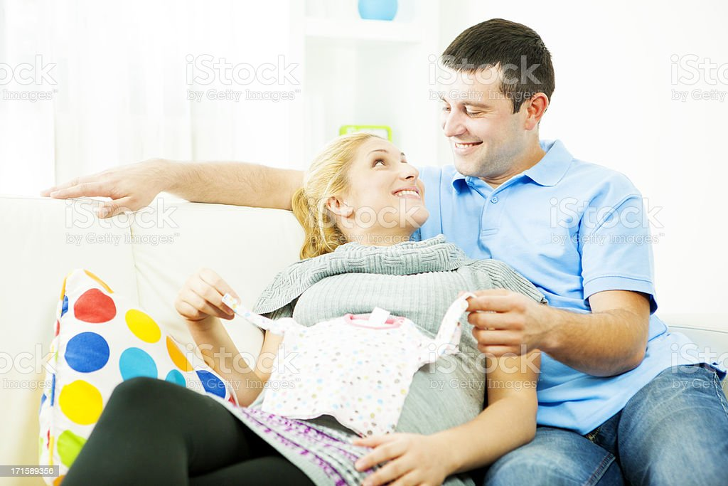 Happy Expecting Couple Looking at baby clothing. royalty-free stock photo