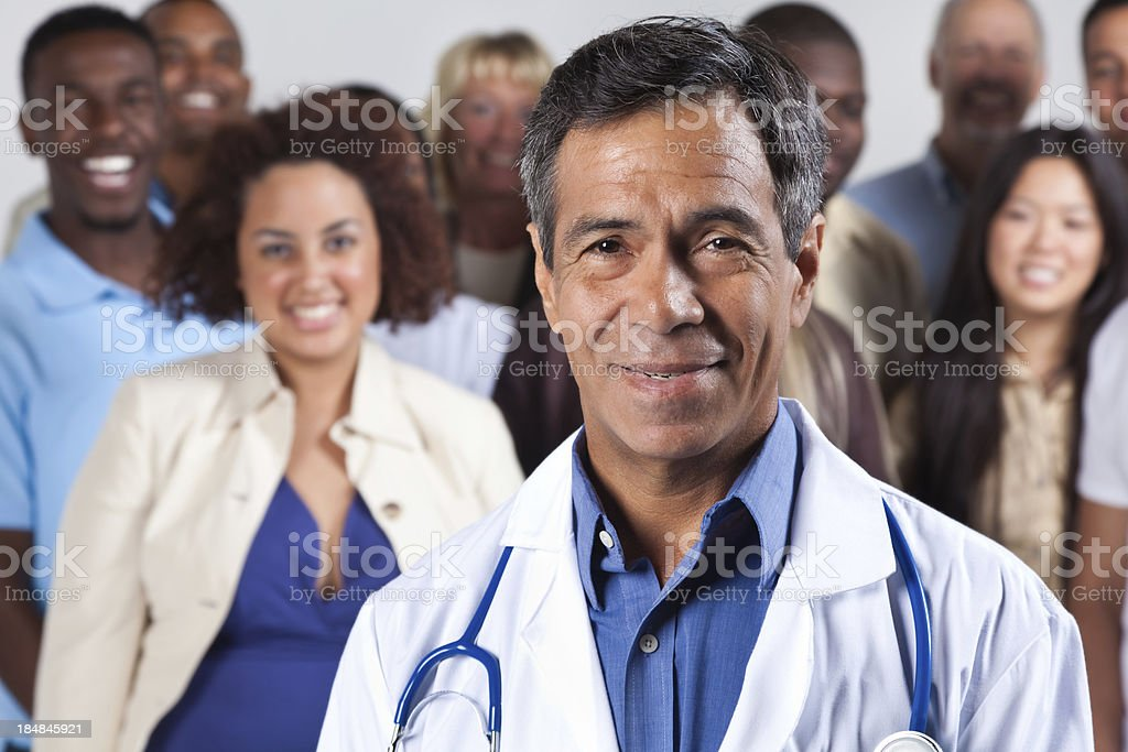 Happy experienced doctor in front, diverse group of patients royalty-free stock photo