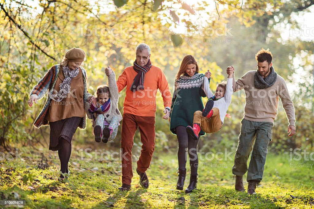 Happy extended family having fun in the park. stock photo