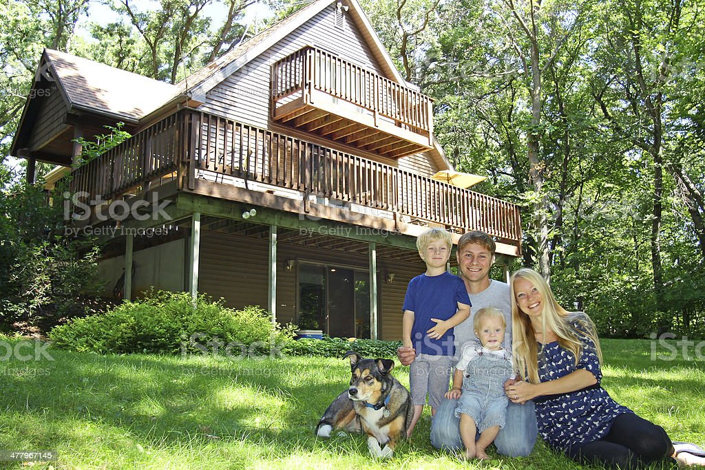 Happy Family at Cabin in Woods stock photo