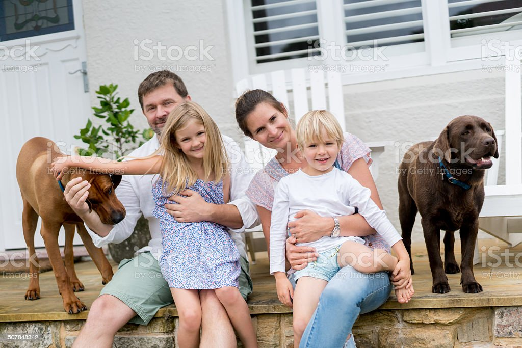 Happy family at home with their dogs stock photo