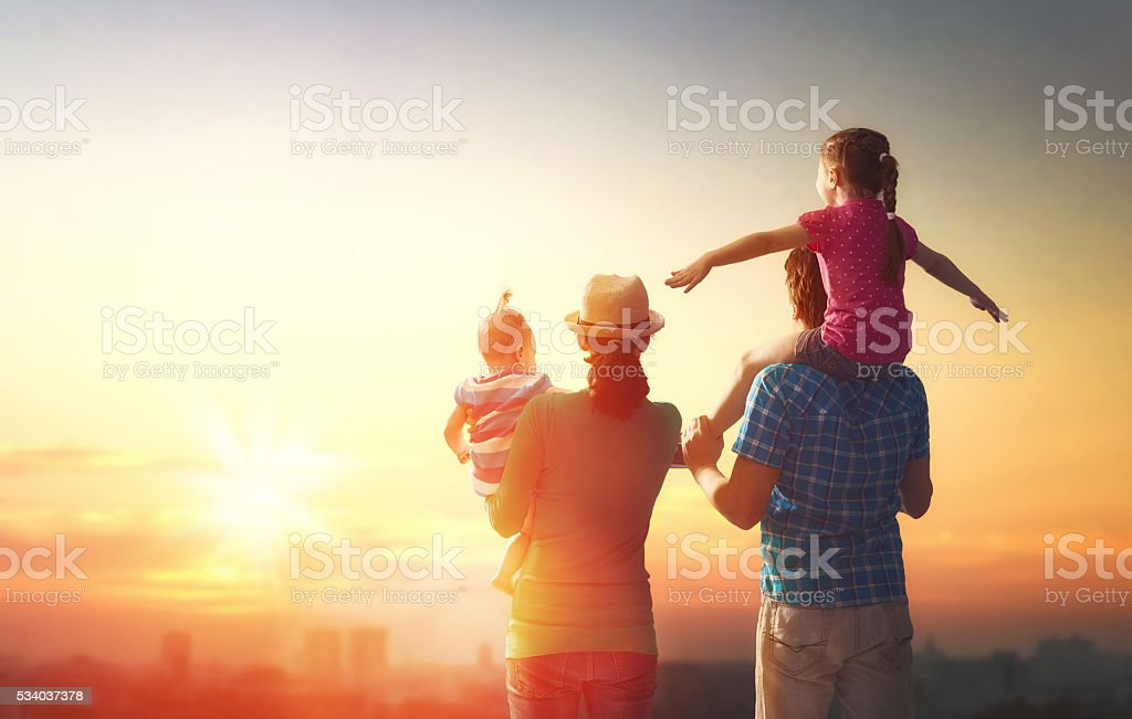 happy family at sunset. father, mother and two children daughters...
