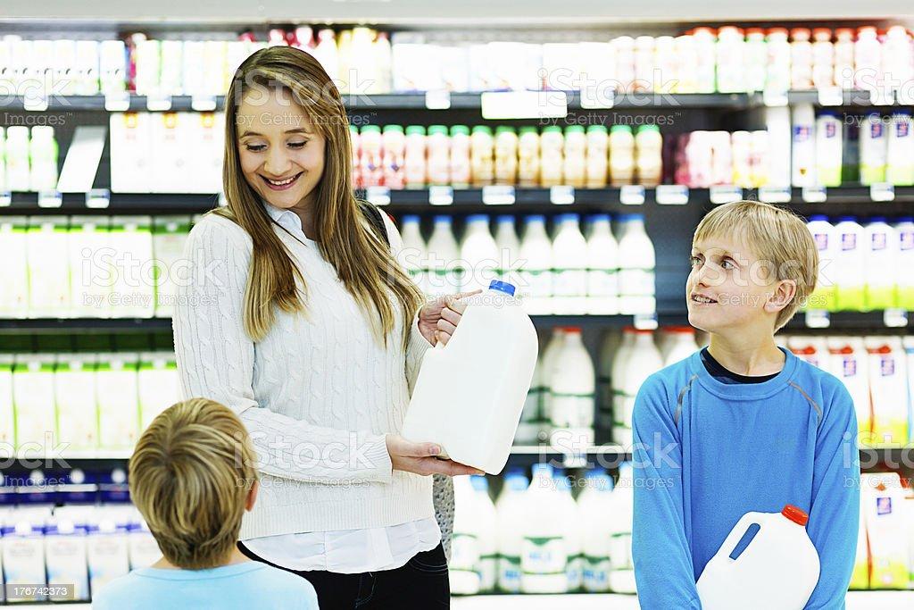 Happy family buying milk in supermarket royalty-free stock photo